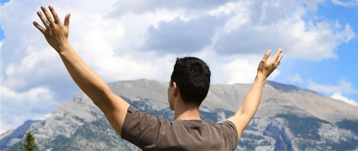 Prayer - Man with lifted hands in front of mountain